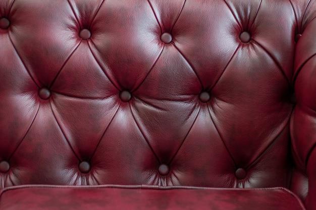 Textura del primer del sofá de cuero rojo del vintage para el fondo.