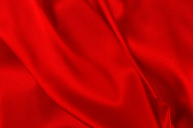 La textura de seda roja y anaranjada o de tela de satén de lujo se puede utilizar como fondo abstracto.