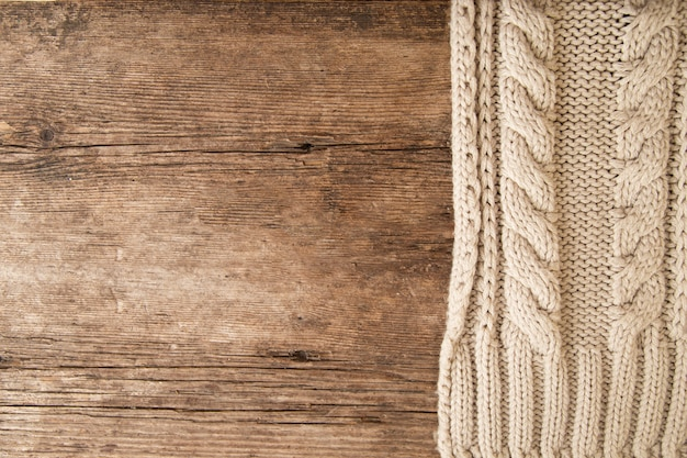 Textura de un suéter de punto beige sobre un fondo de madera. de punto, primer plano