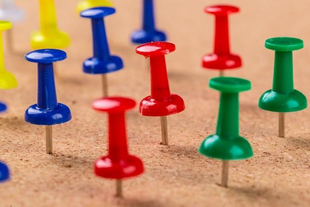 Textura de tablero y alfileres coloridos