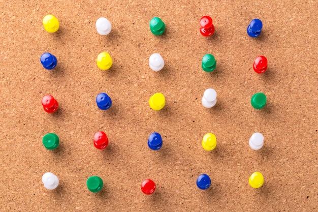 Textura de tablero para el fondo y alfileres de colores
