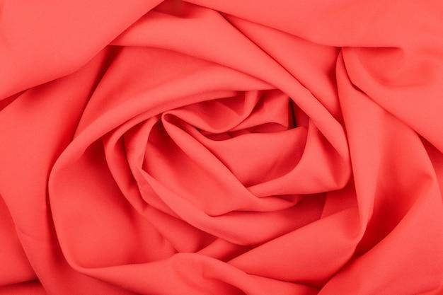 Textura del tejido rojo coral mate con pliegues.