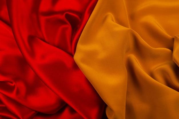 La textura de la tela de lujo de seda o satén roja y naranja se puede utilizar como fondo abstracto.