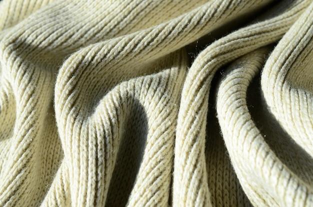 La textura de la tela de un suave suéter de punto amarillo. imagen macro de la estructura de ligaduras en hilos.