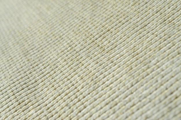 La textura de la tela de un suéter de punto amarillo suave.