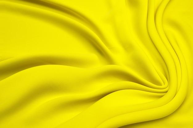 Textura de tela de tela de lujo de seda de satén amarillo claro ondulado elegante liso hermoso, diseño de fondo abstracto. copia espacio