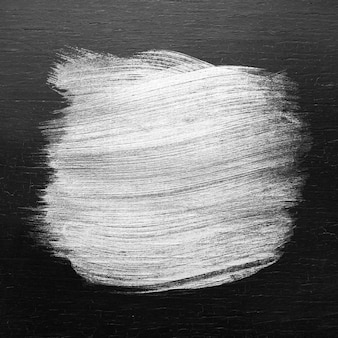 Textura de trazo de pincel de pintura de aceite de plata sobre un fondo de madera coloreada