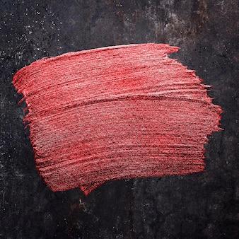 Textura de trazo de pincel de pintura de aceite rojo metálico sobre un fondo negro