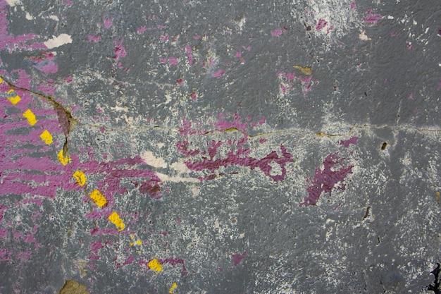 Textura urbana de pintura gris, rosa y amarilla astillada. fondo.