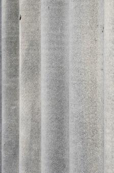 La textura de un viejo techo de casa de asbestos en un pueblo o una vieja valla pintada de pizarra de escalofríos