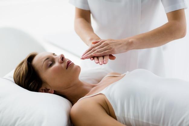 Theparist realizando tratamiento de reiki en mujer