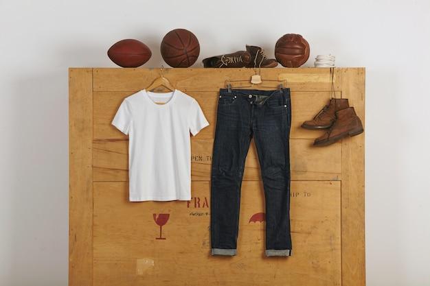 Thirt de algodón en blanco blanco presentado cerca de jeans de orillo japoneses y zapatos de cuero en una caja de carga grande de madera con pelotas de juego vitage en la parte superior