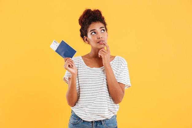 Thoghtful mujer sosteniendo pasaporte internacional aislado sobre amarillo