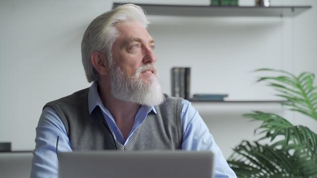 Thoughtfulan anciano hombre de negocios con barba gris pensando en la solución del problema trabajando en una computadora portátil
