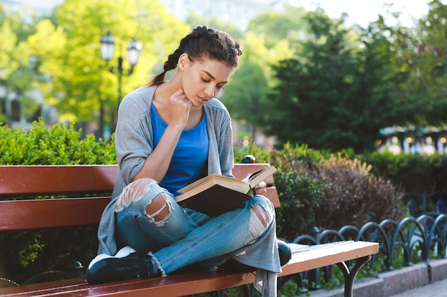 Thouhtful hermosa niña africana leyendo el libro