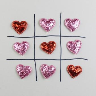Tic-tac-toe con corazones brillantes decorativos