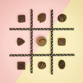 Tick-tack-toe hecha de chocolate y paja sobre fondo en colores pastel. lay flat. concepto de comida sana