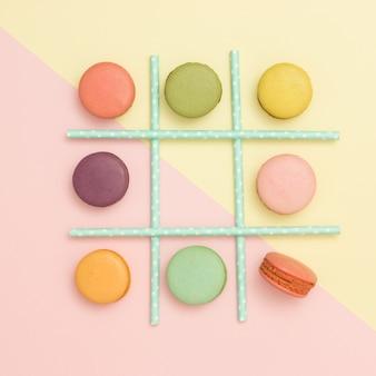 Tick-tack-toe hecha de macarrones y pajitas sobre fondo en colores pastel. lay flat. concepto de comida sana