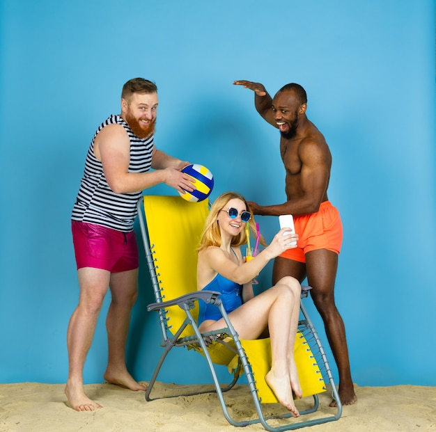 Tiempo de actividad. amigos felices toman selfie, jugando voleibol sobre fondo azul de estudio. concepto de emociones humanas, expresión facial, vacaciones de verano o fin de semana. frío, verano, mar, océano.