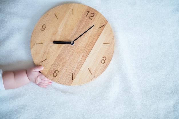 Tiempo para el bebé: la mano del bebé y el reloj de madera