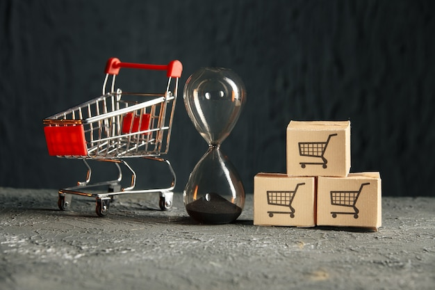 Tiempo para el concepto de compras. carro de compras y reloj de arena. entrega.