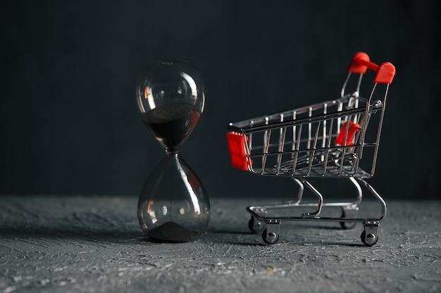 Tiempo para el concepto de compras. carro de compras y reloj de arena. rebaja.