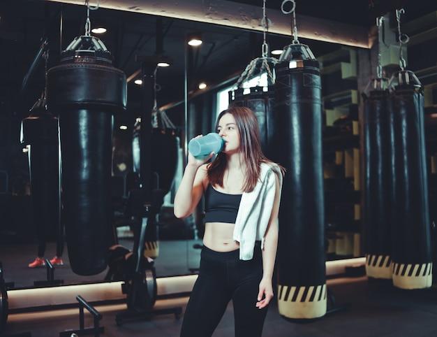 Tiempo de un descanso. chica cansada en ropa deportiva bebe agua de la botella con una toalla