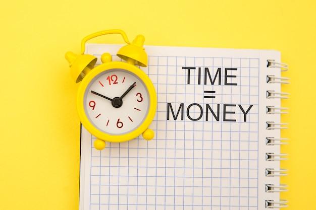 El tiempo es concepto de dinero con reloj de alarma a un lado en amarillo.