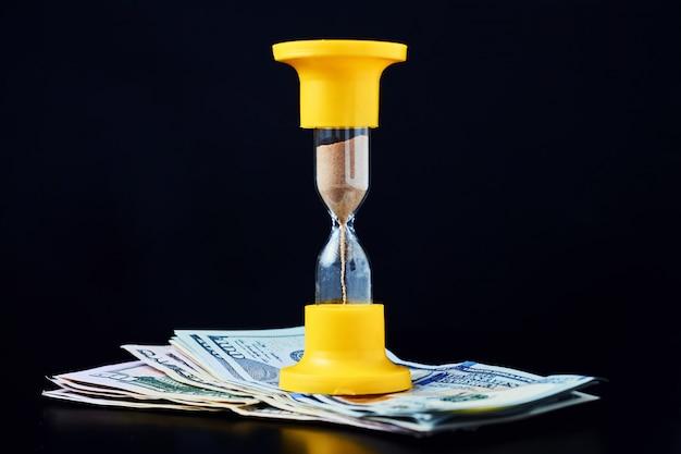 El tiempo es concepto de dinero. reloj de arena amarillo en la pila de billetes de un dólar sobre un fondo oscuro