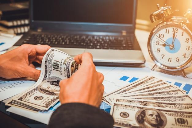 El tiempo es dinero. mano de negocios con reloj de arena reloj y dinero en dólares.