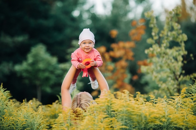 Tiempo feliz juntos. madre jugando con su bebé, sosteniendo al niño en las manos.