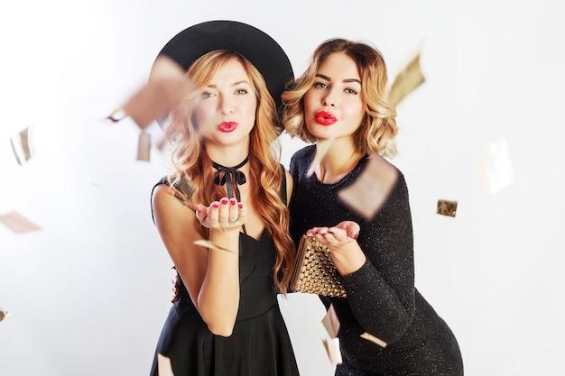 Tiempo de fiesta de dos mejores amigas, mujeres rubias en elegante vestido de cóctel negro posando en estudio sobre fondo blanco. confeti dorado brillante. peinado ondulado.
