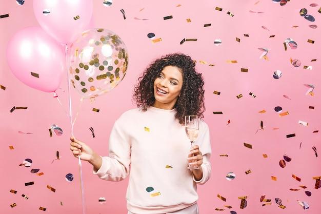 ¡tiempo de fiesta! feliz hermosa mujer afroamericana con copa de champán, globos y confeti cayendo aislado sobre fondo rosa.