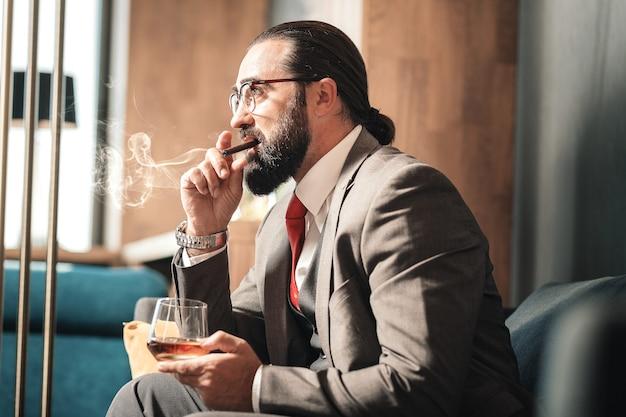 Tiempo de fumar. hombre de pelo oscuro con peinado agradable fumando cigarros y mirando por la ventana