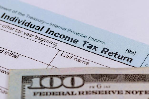 Tiempo de impuestos primer plano de la declaración de impuestos de ee. uu. 1040 con 100 billetes