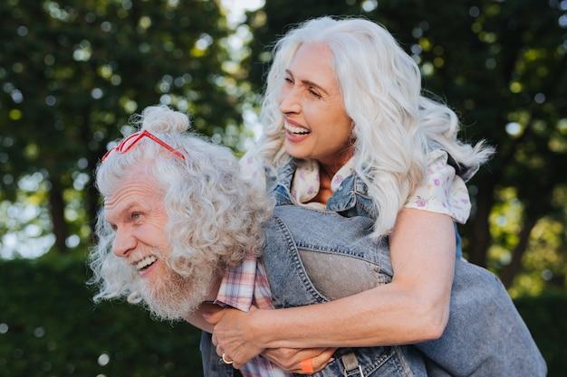 Tiempo juntos. buen hombre feliz que lleva a su esposa mientras pasa un tiempo agradable junto con ella