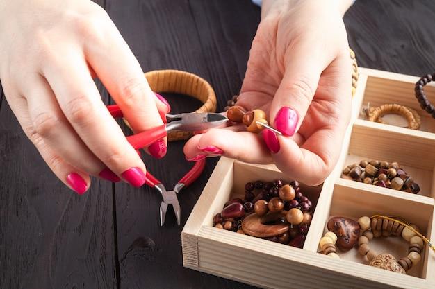 Tiempo libre por la noche haciendo perlas. mujer ocio a domicilio trabajo, concepto de clase magistral