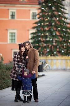 Tiempo de navidad. familia feliz: madre, padre y niña caminando en la ciudad y divirtiéndose