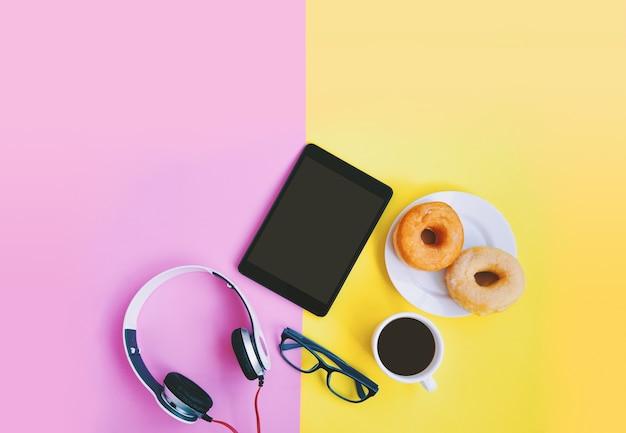 Tiempo de relajación, café, anteojos de donuts, tableta y auriculares en fondo pastel