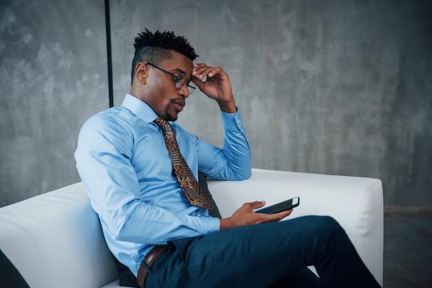 Tiempo de relajación. retrato de joven afroamericano en gafas y ropa clásica sentado en el sofá de cerca