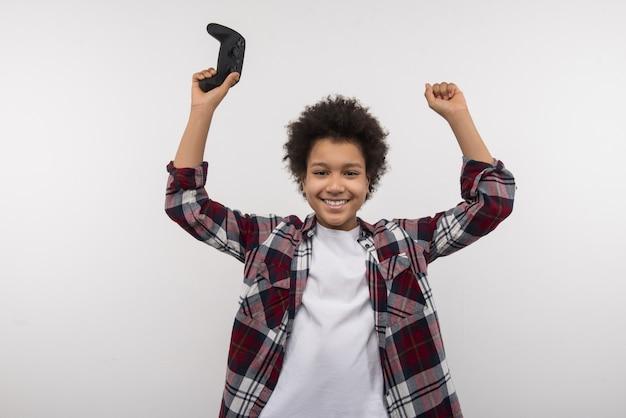 Tiempo para relajarse. niño feliz alegre animando mientras sostiene una consola de videojuegos