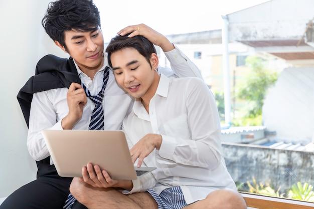 Tiempo romántico y de relajación pareja de homosexuales asiáticos en suite comprando en línea con una computadora portátil juntos en casa