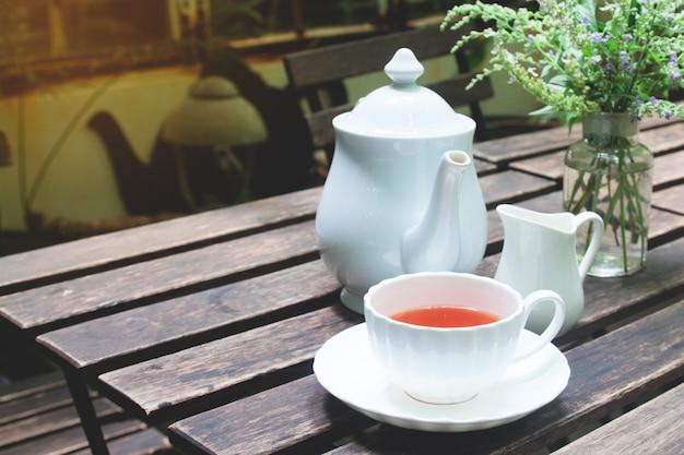 Tiempo del té en la mesa de madera en el jardín de la cabaña