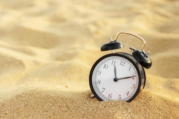 Tiempo de vacaciones, reloj despertador en la arena