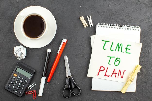 Tiempo de vista superior para planificar escrito en una nota, papel, tijeras, calculadora, taza de té, bolígrafo rojo y marcador negro sobre negro