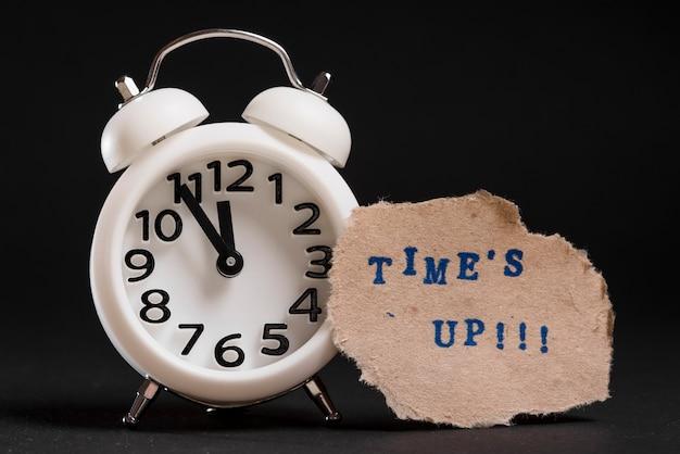 Tiempos de hasta texto en papel marrón roto cerca del reloj de alarma blanco sobre fondo negro
