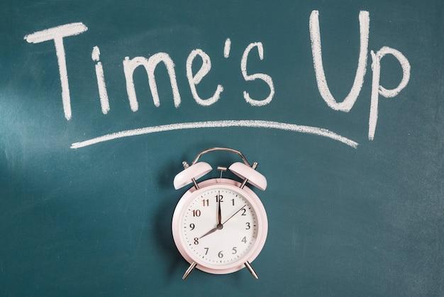 Tiempos hasta texto en pizarra verde con reloj despertador