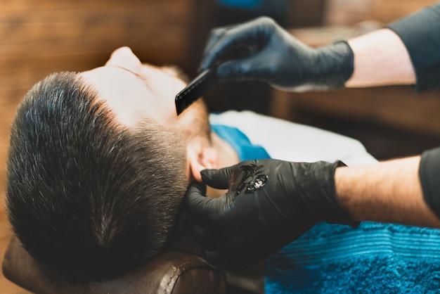 Tienda de belleza para hombres. afeitarse la barba en una barbería. barber se corta la barba con una navaja y una maquinilla. cerrar cortes de pelo brutales. equipamiento de peluquería. enfoque selectivo.