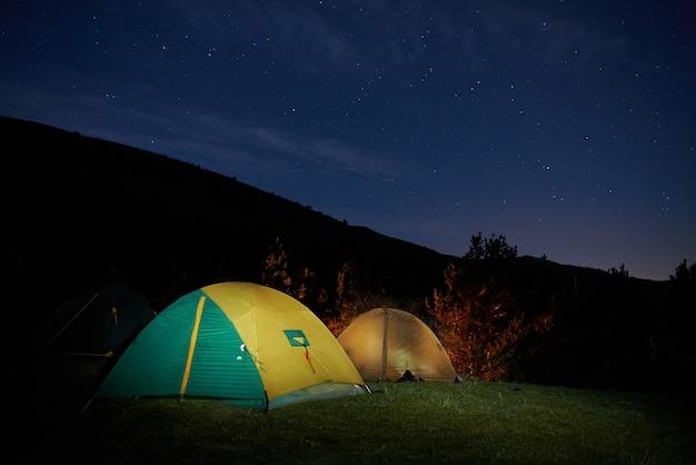 Tienda de campaña amarilla iluminada bajo las estrellas por la noche