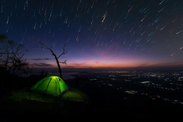 La tienda de campaña brilla intensamente en la montaña debajo de un cielo nocturno, rastros de la estrella del fondo